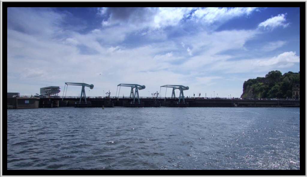 The barrage from the water showing the lock gates and cranes that lift the road way to allow boats in and out..